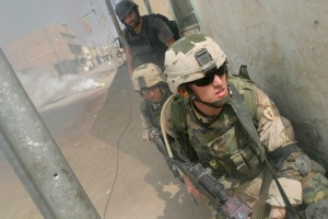 October 1, 2004 - Baquba, Iraq: Time Magazine writer Michael Ware advances with U.S. soldiers with the 25th Infantry Division, 1st battalion, 14th regiment, Alpha Company, 1st Platoon, looks around a corner while a smoke grenade covers his advance during an attack to take back Samarra from insurgent control. The operation circled the city of Samarra with four battalions. After the initial attack the city is to be held with 500 Iraqi National Guard units after the fight. (Max Becherer/Polaris) ///
